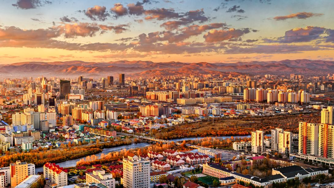 A setting sun paints Ulaanbaatar city and the sky above it in a warm orange, showing it's beauty from an aerial shot.